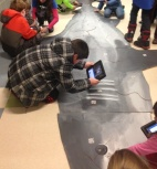 iPads are used to read QR codes that reveal information about shark adaptations.